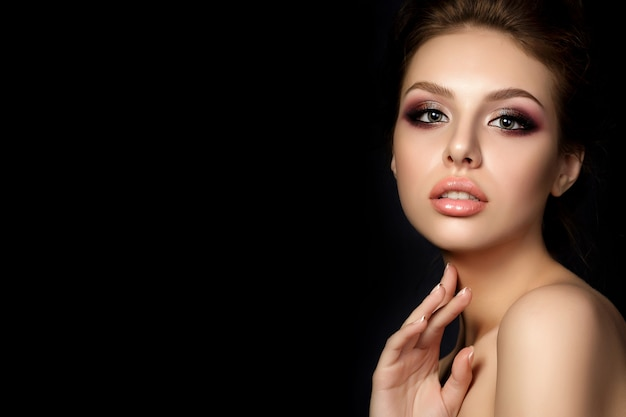 Portrait of young beautiful woman with evening make up touching her neck over black background