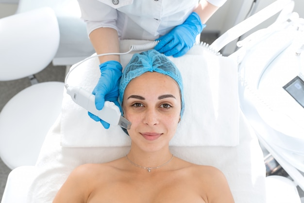 Portrait of a young beautiful woman with facial treatment