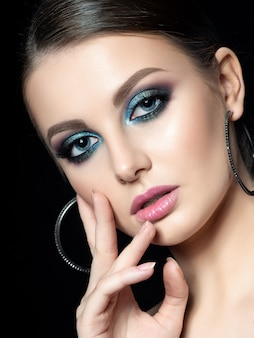 Portrait of young beautiful woman with fashion makeup touching her face. modern blue smokey eyes make up.