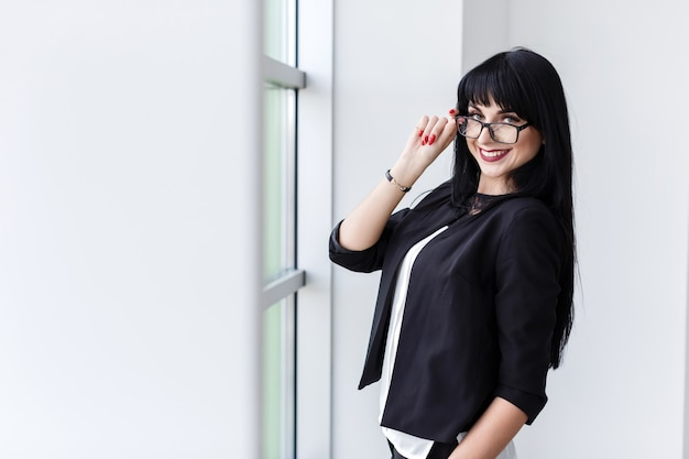 Portrait of young beautiful woman with glasses standing near the window