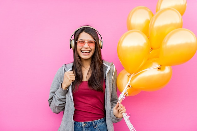 Portrait of young beautiful woman with golden balloons