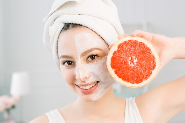 Portrait of young beautiful woman with healthy glow perfect smooth skin holds piece of grapefruit, white towel on the head, white mask on face. natural cosmetics, skincare, facial treatment concept.