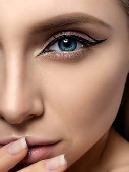 Portrait of young beautiful woman with modern fashion eyeliner wings touching her lips