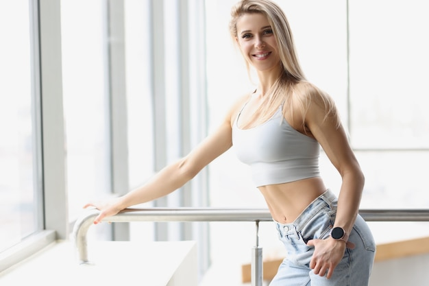 Portrait of young beautiful woman with muscles in sports top and jeans