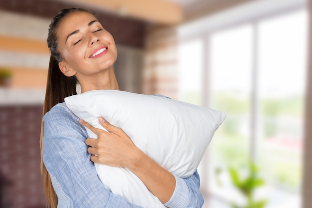Portrait of young beautiful woman with pillow
