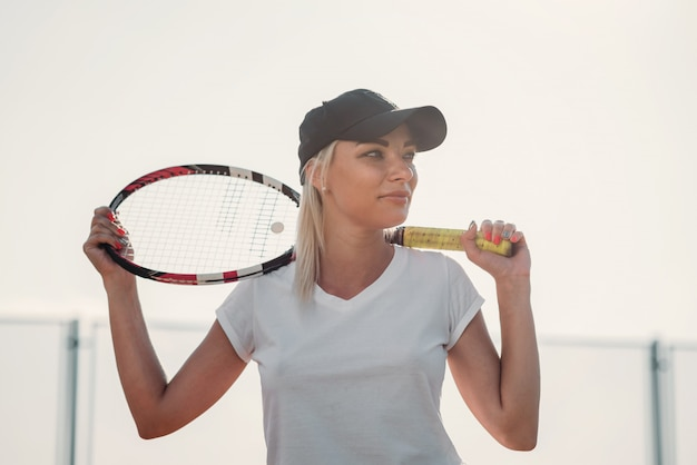 Portrait of young beautiful woman with racket for tennis on a court