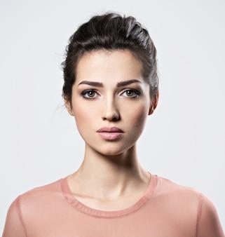 Ritratto di una giovane donna bellissima con trucco occhi fumosi. ragazza adulta abbastanza giovane che propone allo studio. primo piano attraente volto femminile.