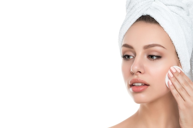 Portrait of young beautiful woman with towel on her hair cleaning makeup from her face with cosmetic pad isolated. cleaning face, perfect skin, skincare and cosmetology concept