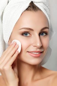 Portrait of young beautiful woman with towel on her hair cleaning makeup from her face with cosmetic pad isolated over white background.