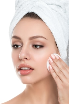 Portrait of young beautiful woman with towel on her hair cleaning makeup from her face with cosmetic pad isolated