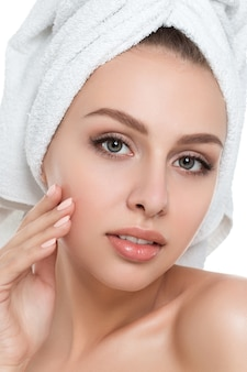 Portrait of young beautiful woman with towel on her hair touching her face isolated