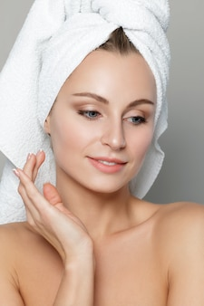 Portrait of young beautiful woman with towel on her head touching her face