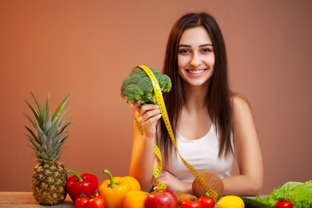 Portrait of young beautiful woman with vegetables, fruits and measuring tape