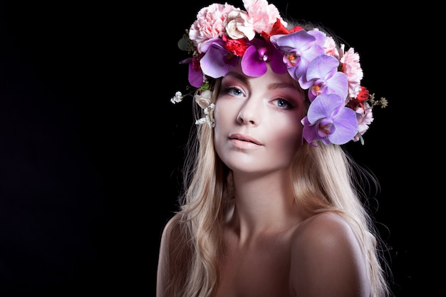 Portrait  young beautiful woman in wreath of flowers