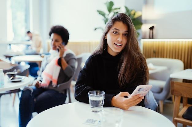 Ritratto di una giovane bella donna lavora su un computer portatile portatile, affascinante studentessa utilizzando net-book mentre è seduto nella caffetteria