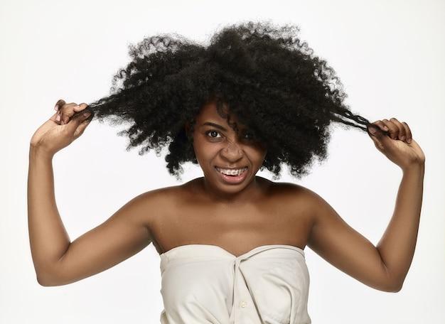 Ritratto di una giovane donna afroamericana nera sorridente con bretelle