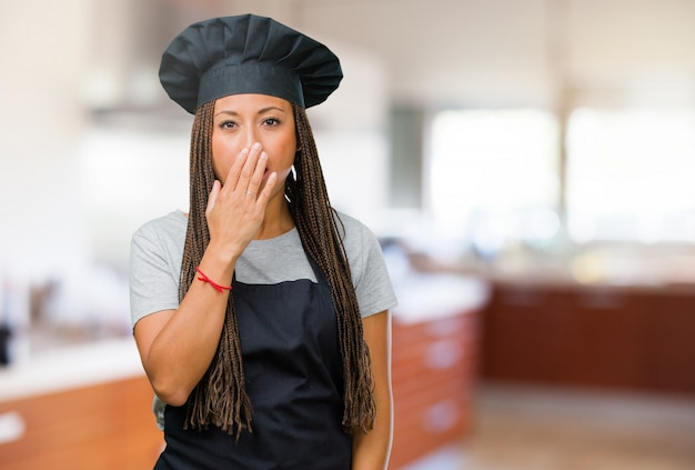 Portrait of a young black baker woman covering mouth, symbol of silence and repression, trying not to say anything