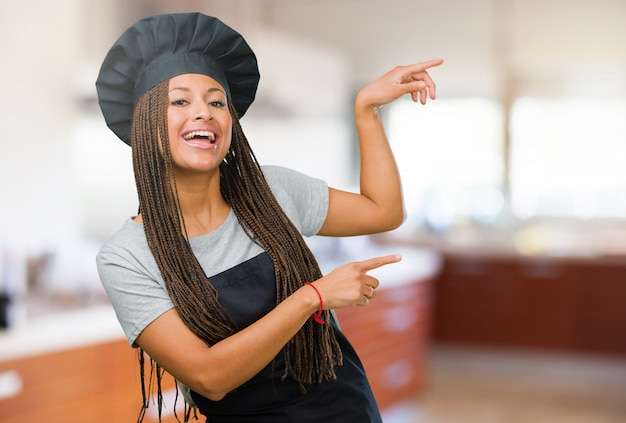 Portrait of a young black baker woman pointing to the side, smiling surprised presenting something