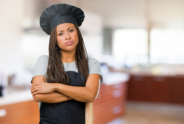 Portrait of a young black baker woman very angry and upset, very tense, screaming furious, negative and crazy
