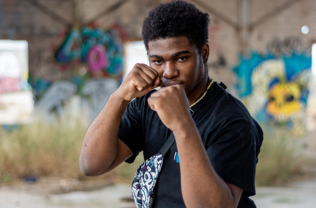 Portrait of young black boy in defense position. graffiti wall background.
