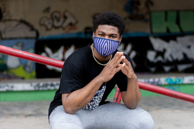 Portrait of young black boy with face mask. graffiti wall background.