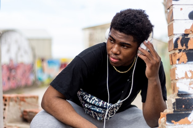 Portrait of young black boy with white headphones. listening to music. abandoned building background.