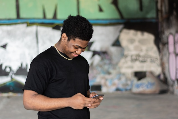 Portrait of a young black boy writing a message on his mobile phone. graffiti wall background.