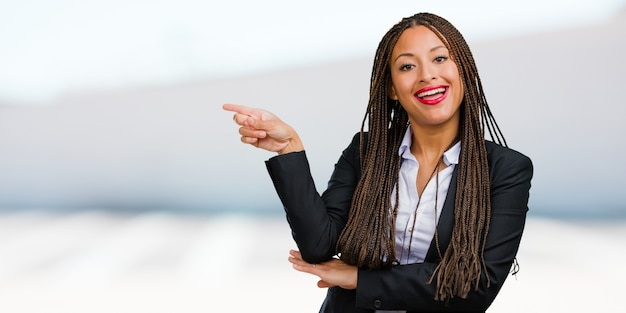 Portrait of a young black business woman pointing to the side, smiling surprised presenting something, natural and casual