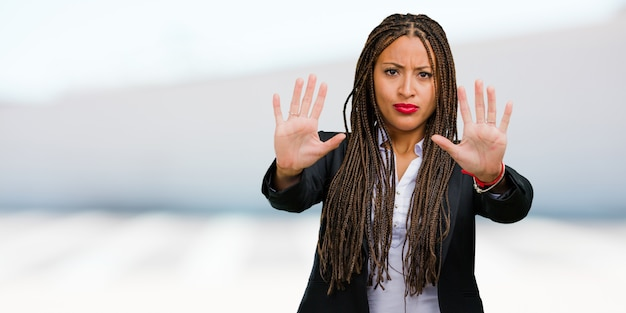 Portrait of a young black business woman serious and determined, putting hand in front, stop gesture, deny concept