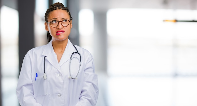 Portrait of a young black doctor woman doubting and confused, thinking of an idea or worried about something