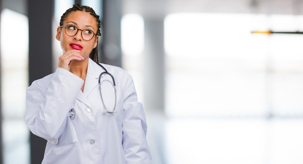 Portrait of a young black doctor woman doubting and confused