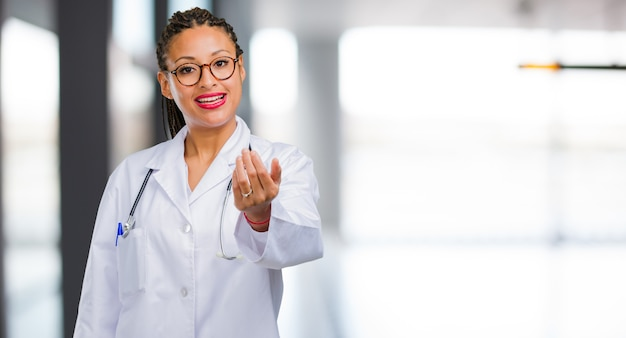 Portrait of a young black doctor woman inviting to come