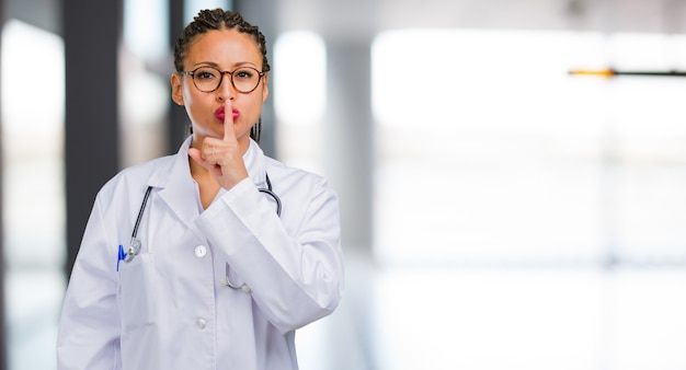 Portrait of a young black doctor woman keeping a secret or asking for silence