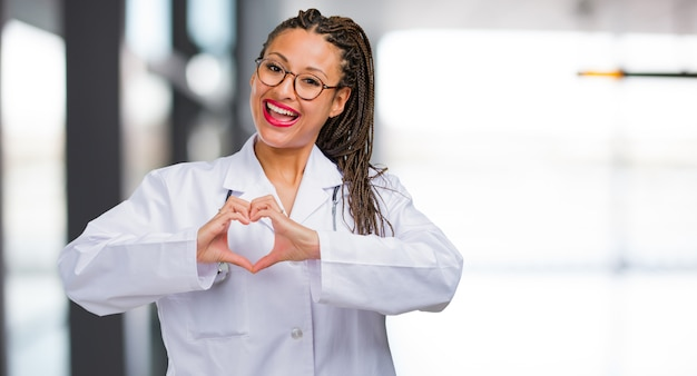 Portrait of a young black doctor woman making a heart with hands