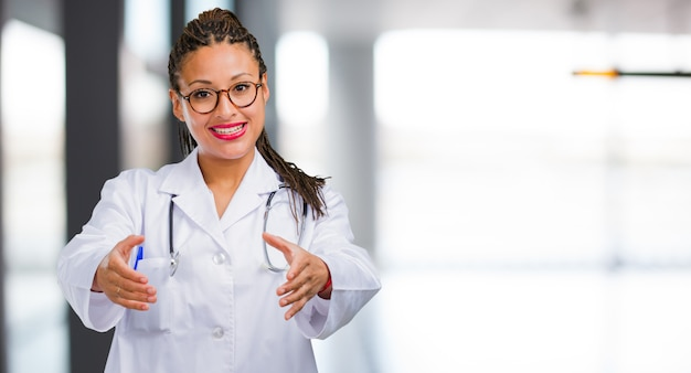 Portrait of a young black doctor woman reaching out to greet someone or gesturing to hel