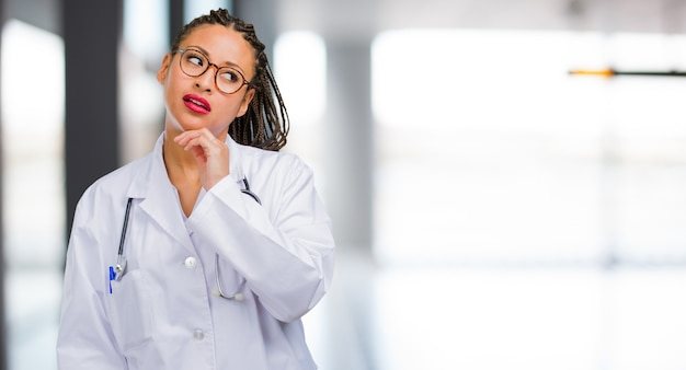 Portrait of a young black doctor woman thinking and looking up, confused about an idea