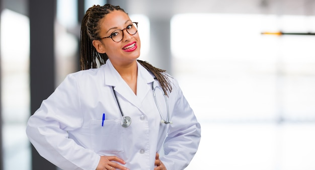 Portrait of a young black doctor woman with hands on hips, standing, relaxed and smiling, very positive and cheerful