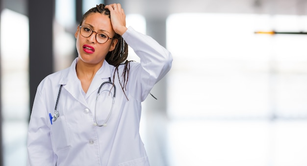 Portrait of a young black doctor woman worried and overwhelmed