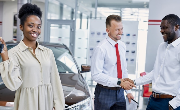 Portrait of young black lady with keys of new car in hands