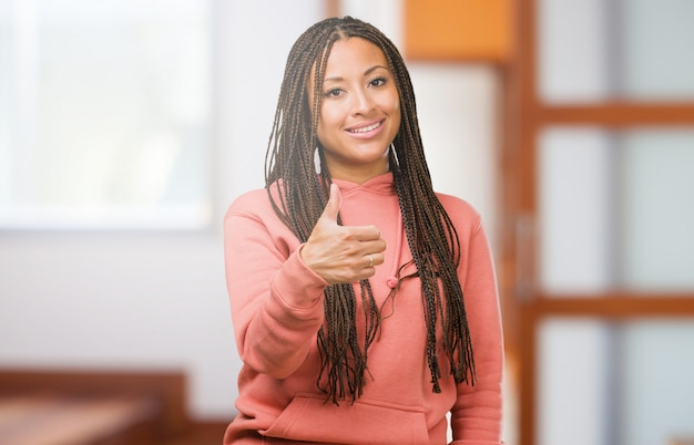 Portrait of a young black woman wearing braids cheerful and excited, smiling and raising her thumb up