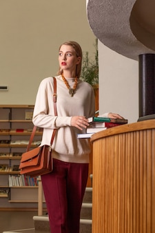 Portrait of young blond cute lady standing by the library desk with books.