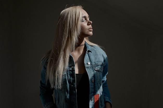 Portrait of young blond woman on dark wall