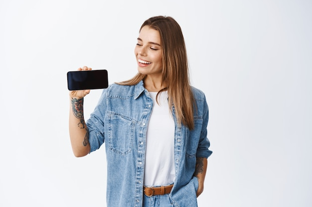 Portrait of young blond woman holding phone horizontally, showing empty smartphone screen for application advertisement, standing over white wall