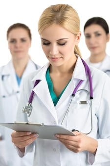 Portrait of young blonde female doctor surrounded by medical team, looking at file with documents. healthcare and medicine concept.