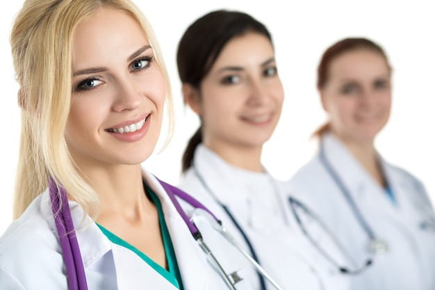 Portrait of young blonde female doctor surrounded by medical team, looking and smiling. healthcare and medicine concept.