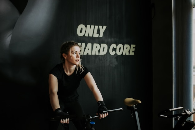 Portrait of a young blonde fit woman on exercise bike in the gym. looking away.
