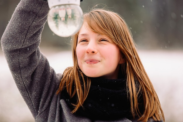Portrait of a young blonde girl holding a crystal winter snow globe, smiling mystery. magical side