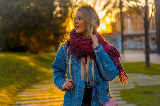 Portrait of a young blonde in the park at sunset