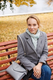 Portrait of young blonde woman in elegant clothes sitting on a bench in autumn park