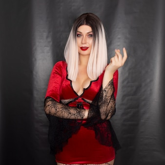 Portrait of a young blonde woman in a red vampire costume